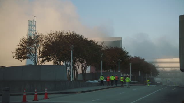 "vidéos et rushes de slo mo. street level view of workers walking towards the aftermath of the implosion of georgia dome stadium ""georgia world congress center"" on november 20, 2017, in downtown atlanta, georgia. - imploding"
