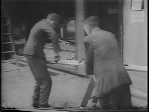 vidéos et rushes de street level views of devastated and wrecked postwar berlin / people pick through the rubble / a man lays bricks in the sidewalk / several people cue... - 1945