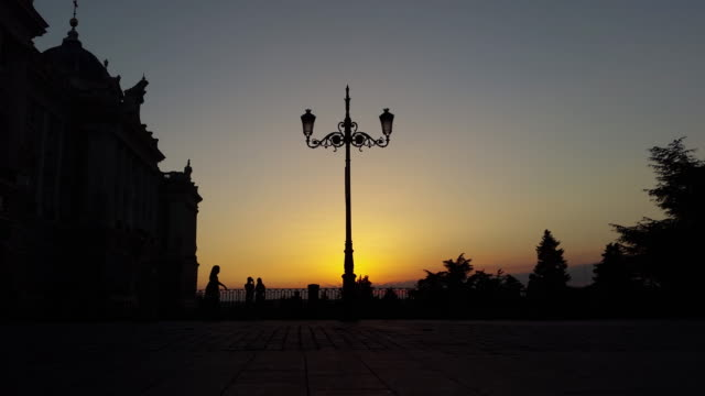 street light with sunset sunrise in madrid spain next to the palace with silhouettes