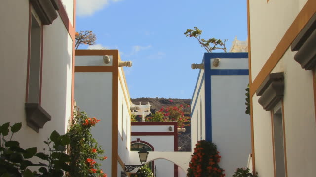 MS ZO Street lights and bougainvillea in alley between brightly colored houses/ Puerto De Mogan, Grand Canary, Canary Islands