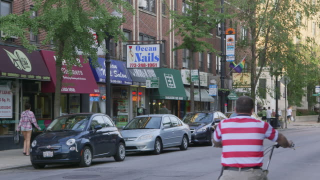 ws street lined with shops day - neighborhood street sign stock videos and b-roll footage