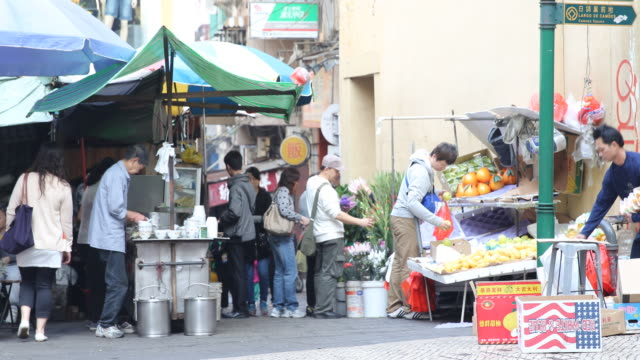 street market and street food vendors on a street of macau. - un giorno nella vita video stock e b–roll