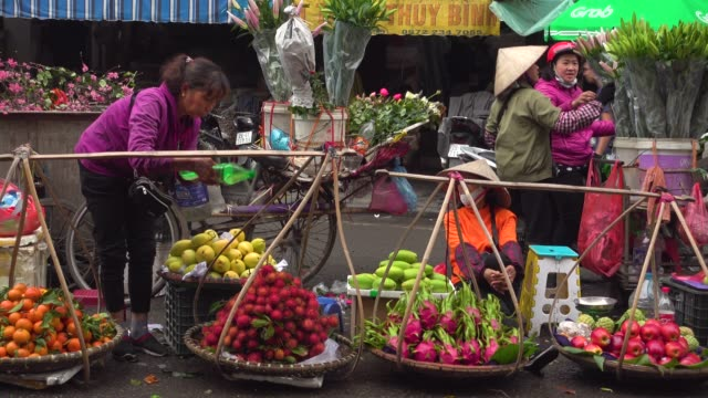 street market at hanoi thien thuat during tet. women with traditional clothing and conical hat selling vegetables from balance shoulder pole - vietnam stock videos & royalty-free footage