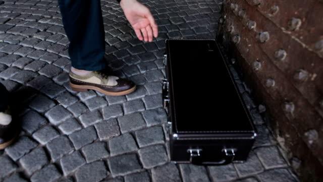 stockvideo's en b-roll-footage met straat muzikant opent een koffer - saxofonist