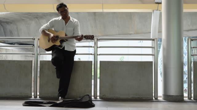street musician playing guitar at sidewalk. - musicista video stock e b–roll