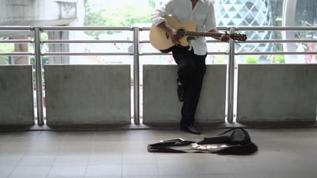 street musician playing guitar at sidewalk. - guitar stock videos & royalty-free footage