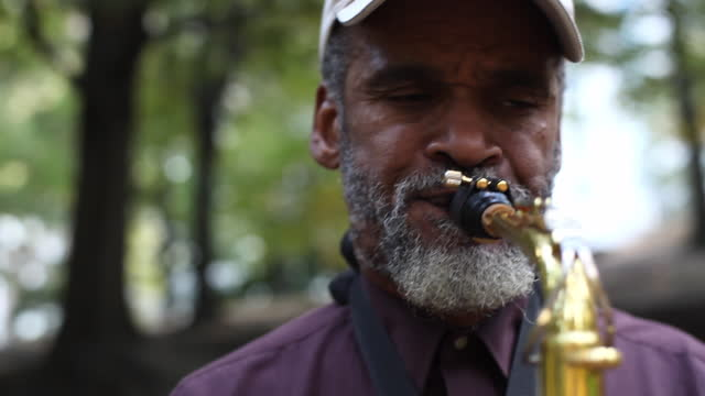 a street musician plays a saxophone in a park. - saxophone stock videos and b-roll footage
