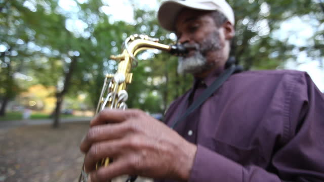 A street musician plays a saxophone in a park.