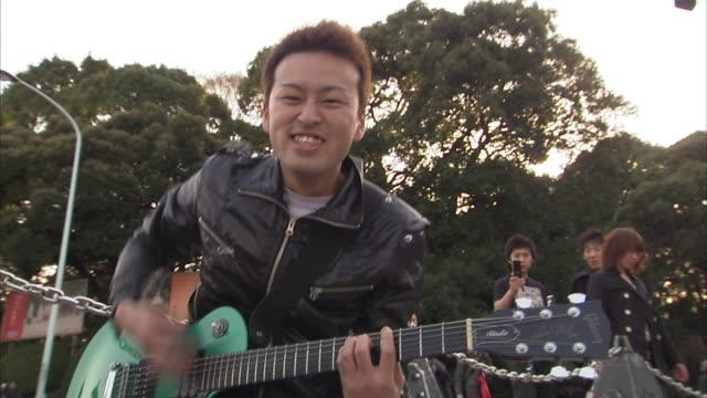 ms street musician plays guitar, tokyo, japan - ミュージシャン点の映像素材/bロール