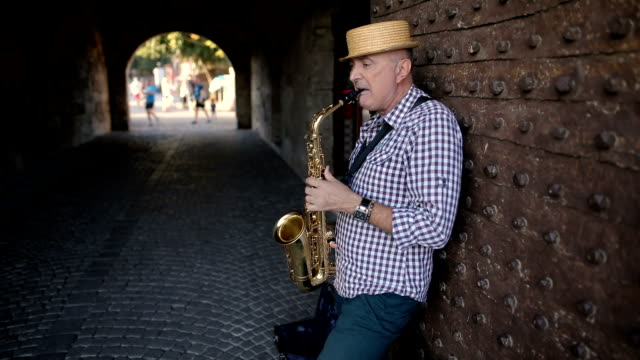 street musician with a hat on his head play saxophone - saxophone stock videos & royalty-free footage