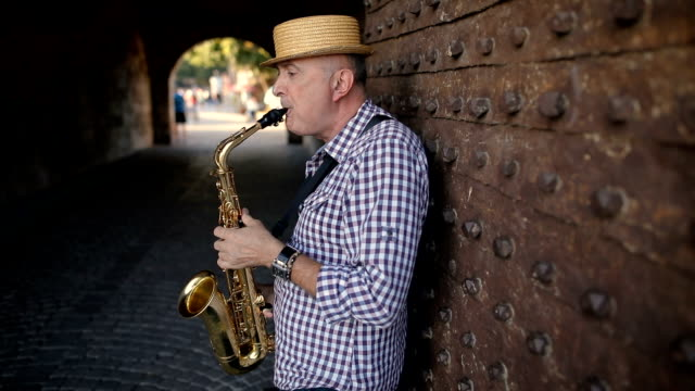 street musician with a hat on his head play saxophone - blues stock videos & royalty-free footage