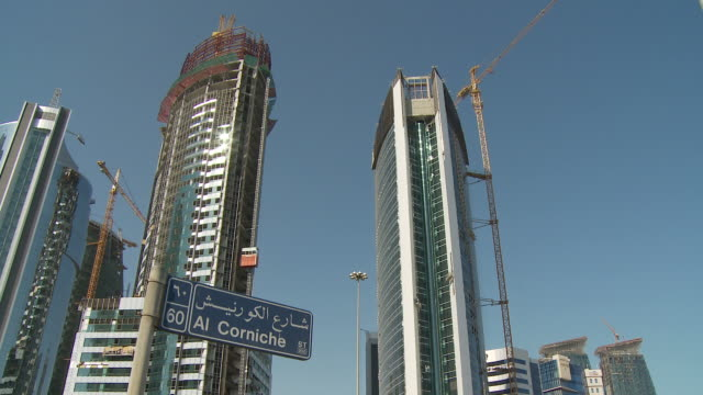 stockvideo's en b-roll-footage met ws td tu street name sign against financial district skyscrapers and traffic on street / doha, qatar - street name sign