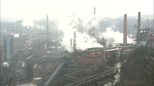 street of office buildings in chong qing covered with smoke;  long shot  zoom in   factory in chong qing with smoke rising.   - luftverschmutzung stock-videos und b-roll-filmmaterial