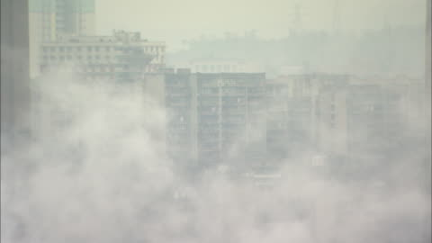 street of office buildings in chong qing covered with smoke; zoom back  factory in chong qing with smoke rising.   long shot chongqing, sichuan province - smog stock videos & royalty-free footage