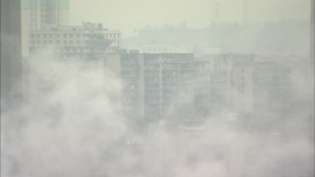 street of office buildings in chong qing covered with smoke; zoom back  factory in chong qing with smoke rising.   long shot chongqing, sichuan province - smog stock-videos und b-roll-filmmaterial