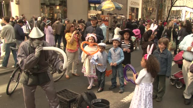 street performer dressed as a tin man performs for crowd in hopes of gathering tips / creates balloon animals for children / nyc's annual easter... - mime artist stock videos & royalty-free footage