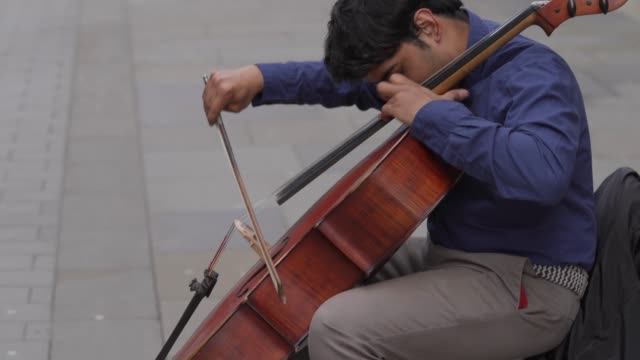 street performer plays classical music on the cello as he sits on an empty street in soho on march 31, 2020 in london, england. like many other... - musician stock videos & royalty-free footage