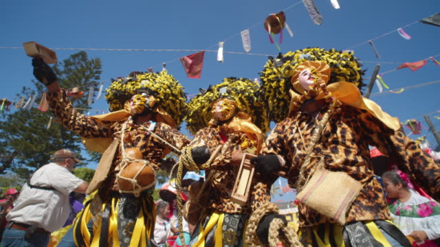 street performers in bright costumes at the zoque coiteco festival parade in chiapas, mexico - chiapas stock-videos und b-roll-filmmaterial
