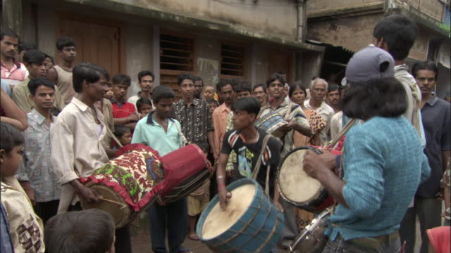 Street performers play colourful drums in the street as a crowd watches Bangladesh. Available in HD.