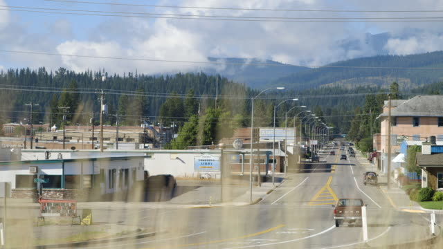 street runs through town of libby, montana, rack focus through weeds - town stock videos & royalty-free footage