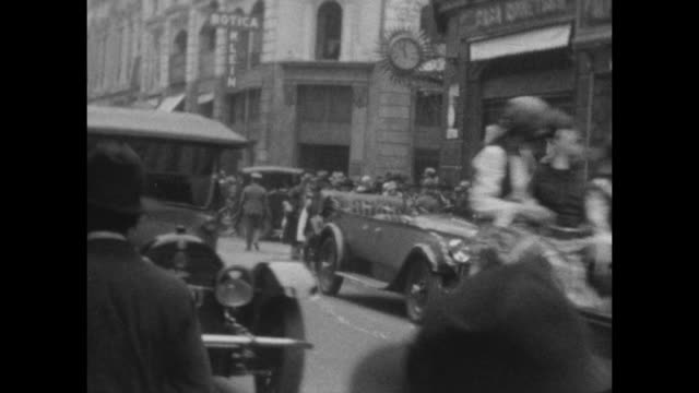 vídeos de stock e filmes b-roll de a street scene as classic cars drive by at carnival in buenes aires 1927. - 1930