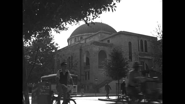 street scene bus, bicycles move on street past the great synagogue in tel aviv; one man rides a bicycle with a sidecar featuring hebrew script /... - sidecar stock videos & royalty-free footage