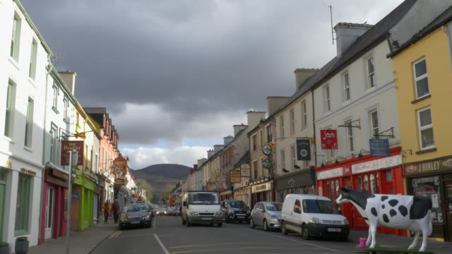 WS  Street scene, colorful village buildings, cow art, nice clouds, Kenmare, County Kerry, Ireland