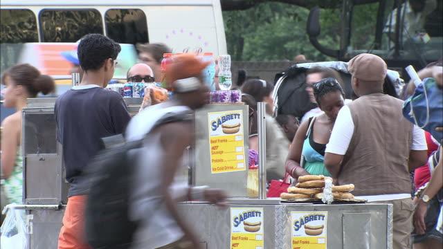 vídeos de stock e filmes b-roll de ms, street scene, hotdog stand, fifth avenue, new york city, new york, usa - feirante
