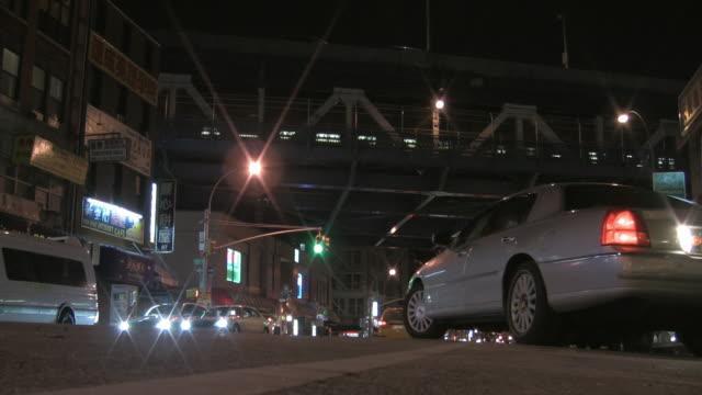 MS, Street scene in Chinatown at night, elevated train crossing bridge, New York City, New York, USA