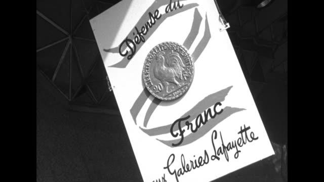 "vídeos y material grabado en eventos de stock de street scene in paris / people at store entrance under ""defense du franc, galeries lafayette"" sign with a 20 franc coin featuring a rooster / women... - gran almacén"