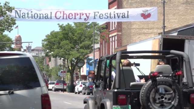 vidéos et rushes de street scene in traverse city michigan with national cherry festival sign hanging across street cars pass - traverse city
