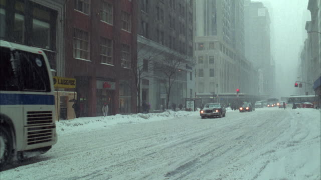 ws tu street scene in winter with empire state building, blizzard / manhattan, new york, usa - anno 1994 video stock e b–roll