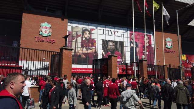 vidéos et rushes de street scene outside the kop end of anfield showing crowds of liverpool fans walking along the street before liverpool's final premier league match... - ambiance format raw