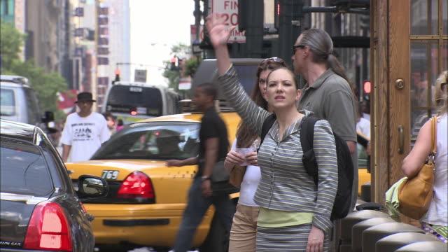MS, Street scene, three people hailing cab, New York City, New York, USA