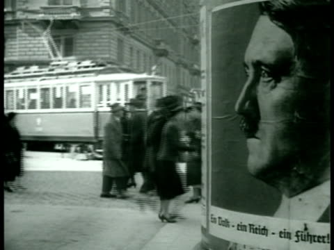 stockvideo's en b-roll-footage met street scene w/ large poster of hitler profile fg soldiers moving in trucks in city man wearing hitler poster around neck troops in street soldier... - 1938