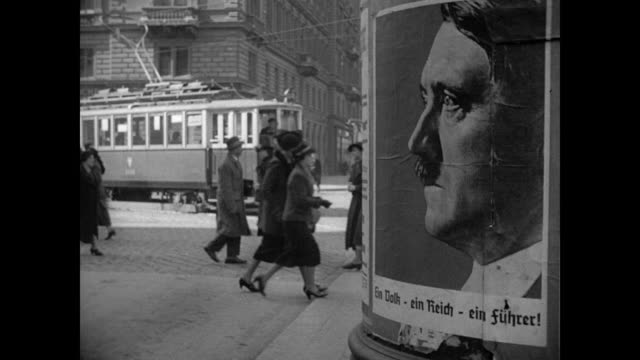 Street scene w/ large poster of Hitler profile FG / Soldiers moving in trucks in city / Man WEARING Hitler poster around neck / Troops in street...