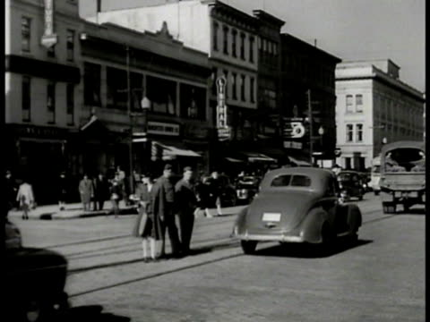 street scene w/ military truck passing man & women in military uniforms crossing street. door sign: war manpower commission us employment service.... - file clerk stock videos & royalty-free footage