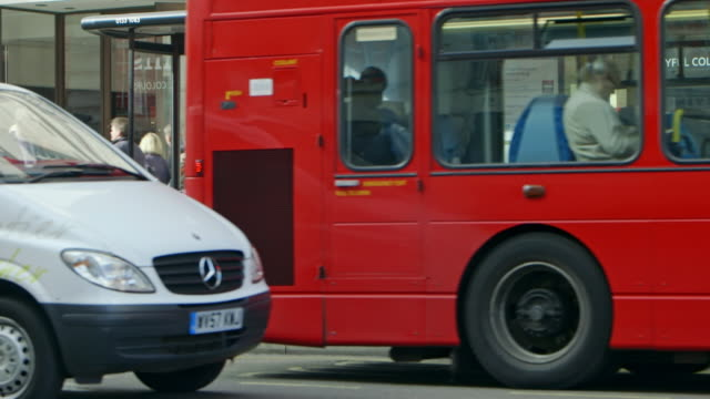 cu zo ms street scene with cars and double-decker buses / london, england, united kingdom - バス停留所点の映像素材/bロール