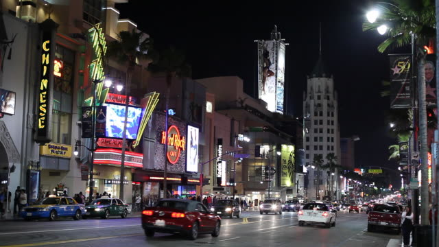 WS Street scene with First National Bank Building in background, night / Hollywood, Los Angeles, California, USA