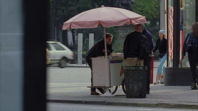 ws street scene with people around hot dog stand / manhattan, new york, usa - 角点の映像素材/bロール