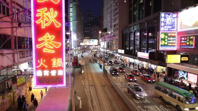 WS HA Street scene with traffic and illuminated neon signs at night / Hong Kong, China