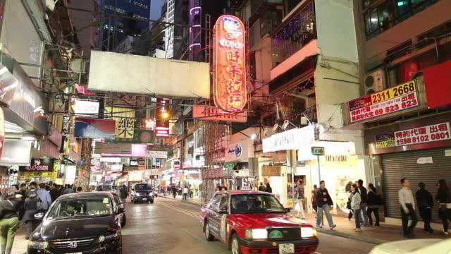WS Street scene with traffic and illuminated neon signs at night / Hong Kong, China