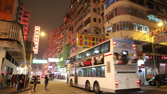 ws street scene with traffic and illuminated neon signs at night / hong kong, china - ladenschild stock-videos und b-roll-filmmaterial