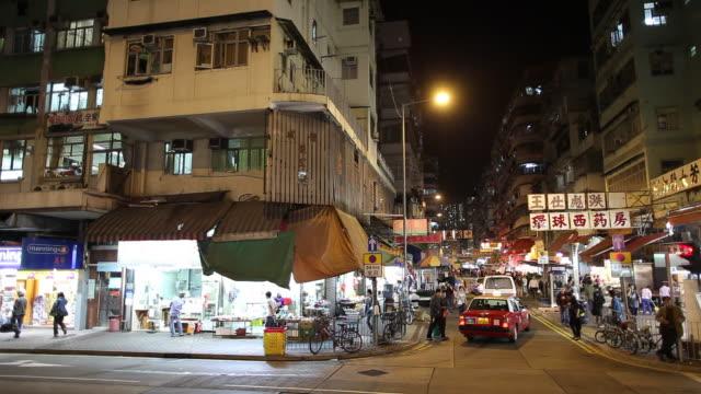 ws street scene with traffic and neons illuminated at night / hong kong, china - butiksskylt bildbanksvideor och videomaterial från bakom kulisserna