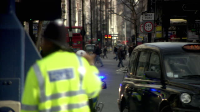 ms r/f street scene with traffic police directing traffic / london, uk - uk video stock e b–roll