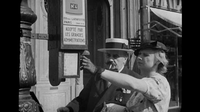 vídeos y material grabado en eventos de stock de ms street scenes and people taking tickets and waiting for bus  / paris, france - 1930