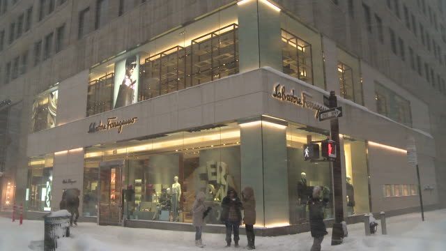street scenes from the blizzard of 2016 / exterior shot of salvatore ferragamo on 5th ave. during a snowstorm / tourists walk past the store trudging... - salvatore ferragamo stock videos & royalty-free footage