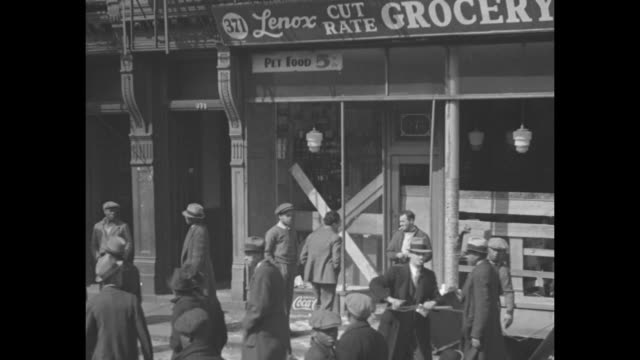 street scenes harlem, ny, with storefronts, pedestrians, traffic / grocery store on lenox avenue with boards covering portions of windows where glass... - ハーレム点の映像素材/bロール