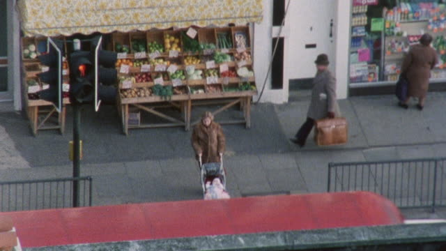 stockvideo's en b-roll-footage met 1983 montage street scenes of children playing and pedestrians walking in kentish town / london, england - 1983