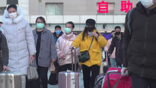 street scenes outside beijing railway station with people wearing face masks during the coronavirus outbreak - corona stock-videos und b-roll-filmmaterial